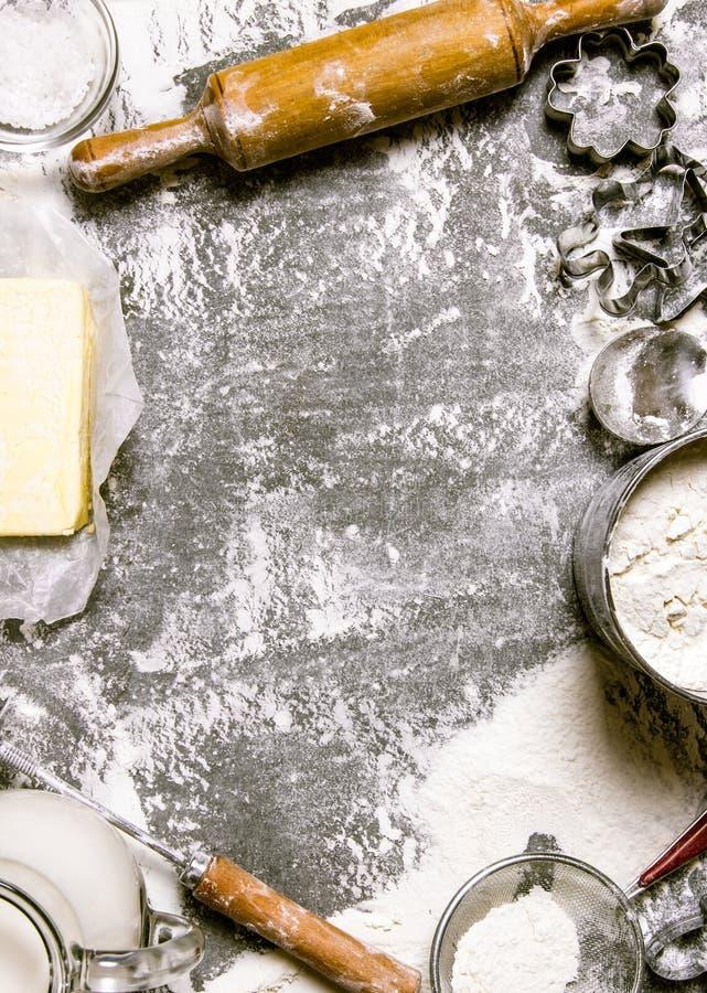 Προετοιμασία της ζύμης Συστατικά για τη ζύμη - αλεύρι, βούτυρο, γάλα, και διάφορα εργαλεία στοκ εικόνα