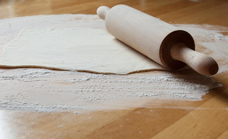 Προετοιμασία της πίτας (η ζύμη και η κυλώντας καρφίτσα στον πίνακα) στοκ φωτογραφία