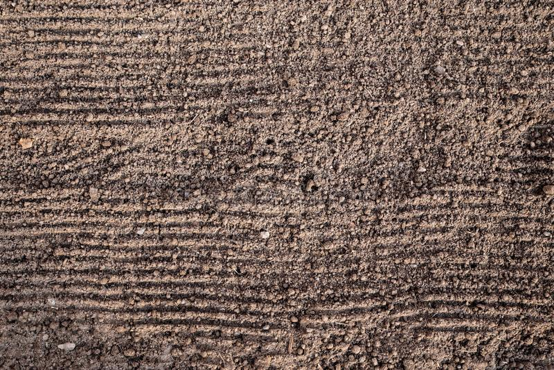 Προετοιμασία του εδάφους πρίν φυτεύει Η σύσταση του εδάφους με τα οριζόντια αυλάκια από την τσουγκράνα, έτοιμη να προσγειωθεί Υγρ στοκ φωτογραφία