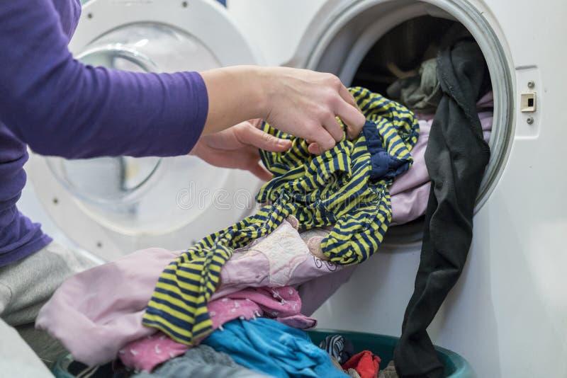 Προετοιμασία του κύκλου πλυσίματος Πλυντήριο, χέρια και ενδύματα στοκ φωτογραφία με δικαίωμα ελεύθερης χρήσης