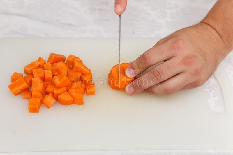 Προετοιμασία τροφίμων - που κόβει το carrott με το μαχαίρι στο άσπρο β στοκ εικόνες