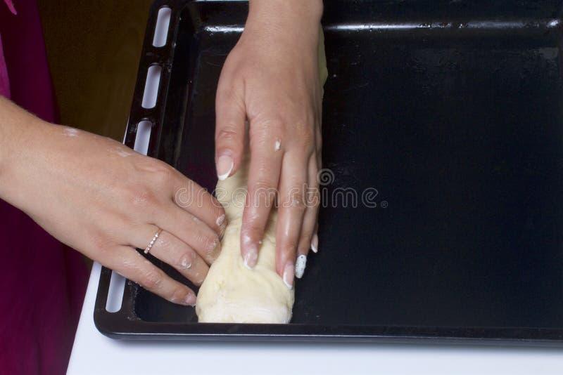 Προετοιμασία των ρόλων κανέλας Η γυναίκα βάζει την κυλημένη ζύμη σε έναν δίσκο ψησίματος στοκ φωτογραφία