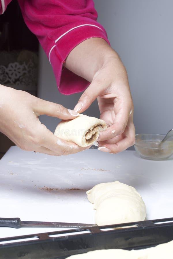 Προετοιμασία των ρόλων κανέλας Μια γυναίκα βάζει τα κουλούρια των κουλουριών σε έναν δίσκο ψησίματος στοκ φωτογραφία με δικαίωμα ελεύθερης χρήσης