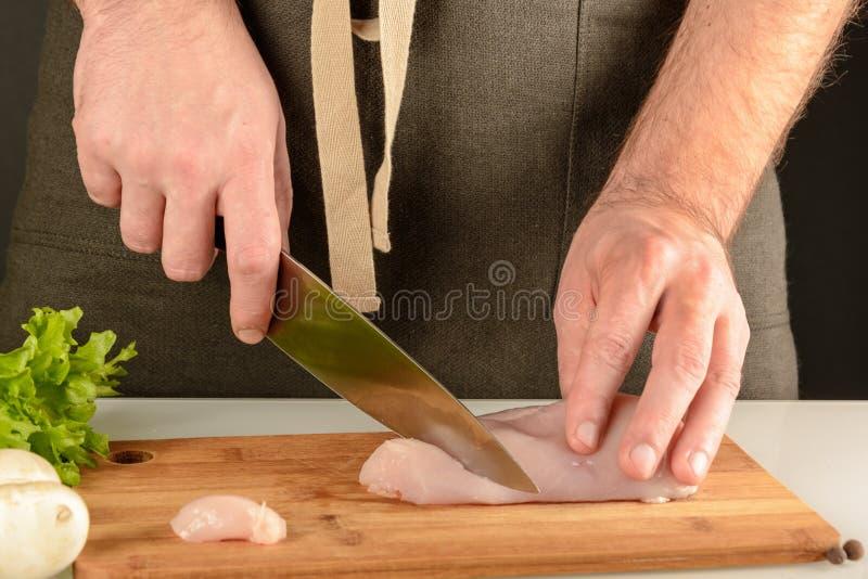 Προετοιμασία των τροφίμων Ένα άτομο σε μια ποδιά είναι τέμνον κρέας σε έναν ξύλινο πίνακα Κατασκευή κοτόπουλου στοκ φωτογραφία