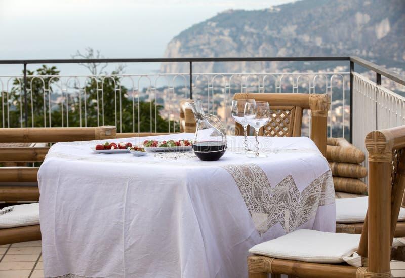 Προετοιμασμένος για τον πίνακα βραδυνού στο πεζούλι που αγνοεί τον κόλπο της Νάπολης και του Βεζούβιου Σορέντο στοκ εικόνα