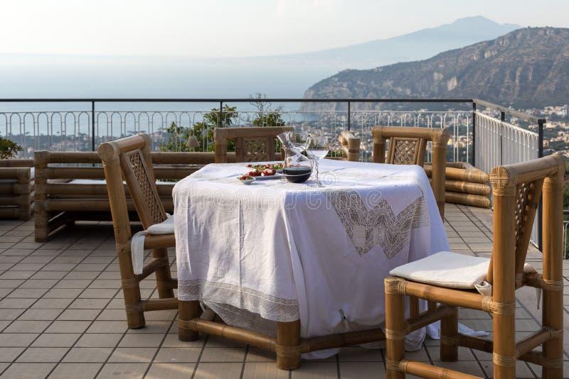 Προετοιμασμένος για τον πίνακα βραδυνού στο πεζούλι που αγνοεί τον κόλπο της Νάπολης και του Βεζούβιου Σορέντο στοκ φωτογραφίες