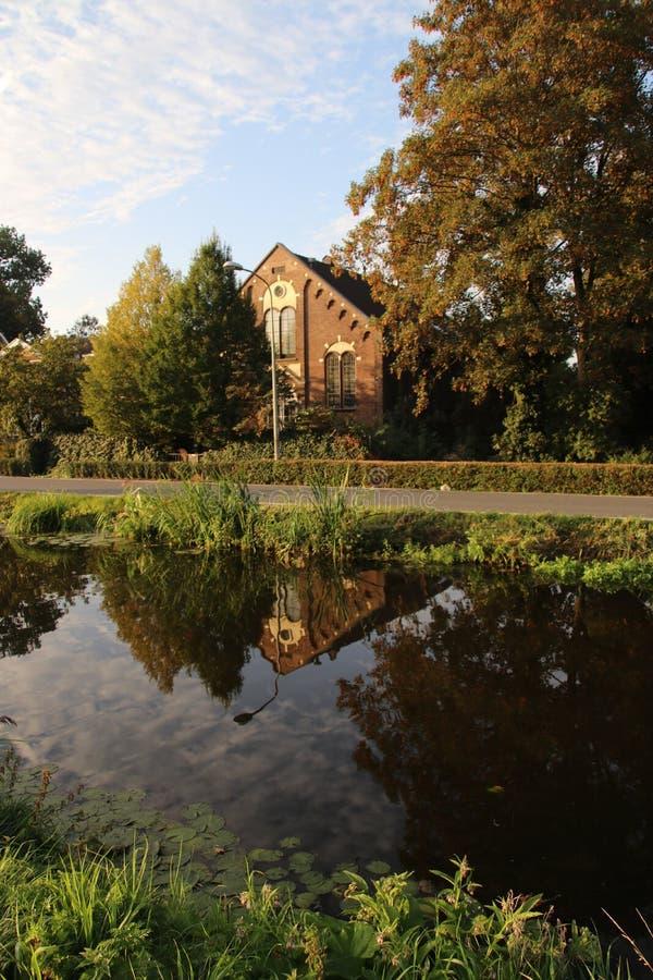 Προηγούμενη εκκλησία που έγινε θέση διαβίωσης στον ήλιο πρωινού και απεικόνιση στο νερό στο κρησφύγετο IJssel Nieuwerkerk aan στι στοκ φωτογραφία με δικαίωμα ελεύθερης χρήσης