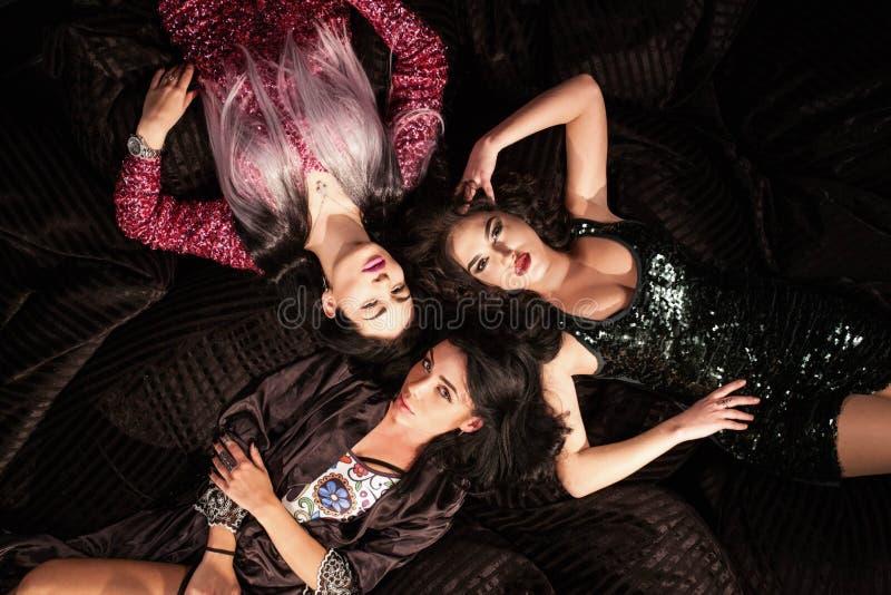 Προκλητικά κορίτσια που θέτουν για τη κάμερα που βρίσκεται στα softbags Γυναίκες που φορούν τα όμορφα φορέματα στοκ εικόνες
