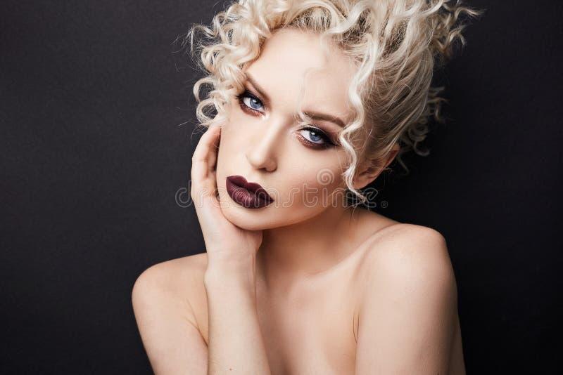 Προκλητική γυμνή νέα γυναίκα με τα σκούρο κόκκινο πλήρη χείλια και με τα όμορφα μπλε μάτια, με την ξανθούς σγουρούς τρίχα και τον στοκ φωτογραφίες