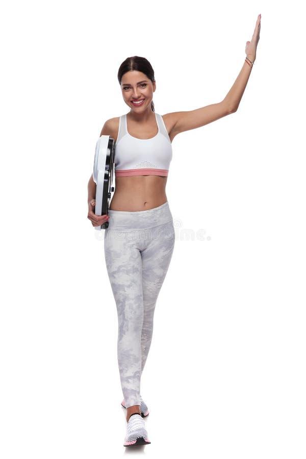 Προκλητική γυναίκα ικανότητας που περπατά με την κλίμακα και το χέρι επάνω στοκ εικόνα