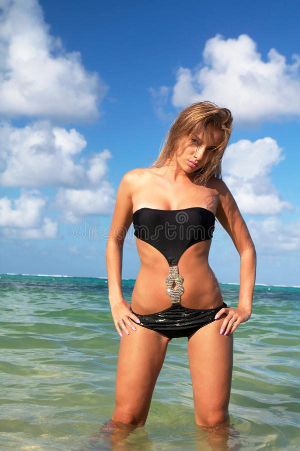Προκλητική γυναίκα μαύρο bikini στην παραλία στοκ φωτογραφία