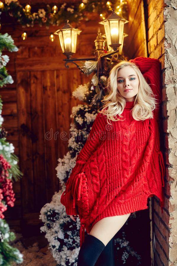 Προκλητική γυναίκα μόδας ο ξανθός στο κόκκινο πουλόβερ, έχοντας τη διασκέδαση και θέτοντας ενάντια στο χριστουγεννιάτικο δέντρο κ στοκ εικόνες
