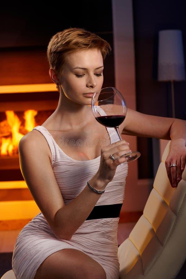 Προκλητική γυναίκα που απολαμβάνει το ποτήρι του κρασιού στοκ εικόνα