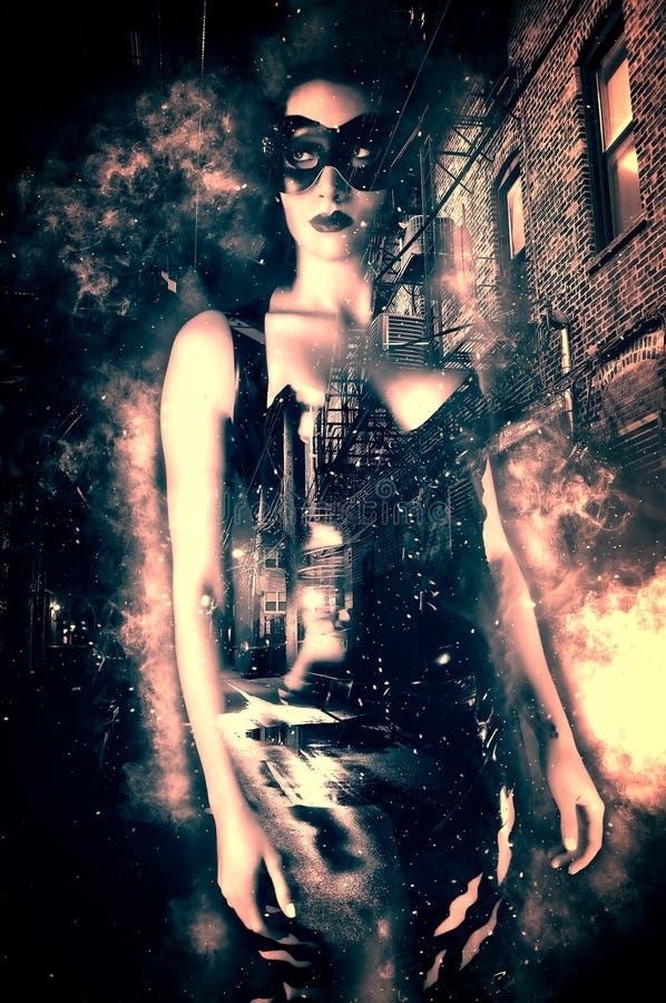 Προκλητική γυναίκα που φορά μια ενετική μάσκα και ένα σφιχτό κοστούμι λατέξ σε μια σκοτεινή αλέα πόλεων στοκ φωτογραφίες