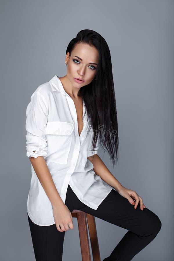 Προκλητική γυναίκα στο άσπρο πουκάμισο σε ένα γκρίζο υπόβαθρο στοκ φωτογραφία