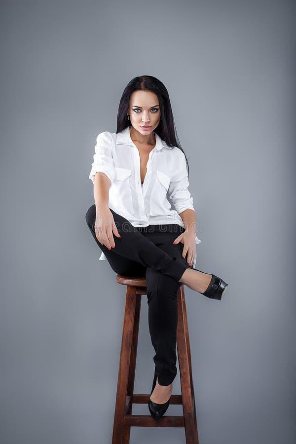 Προκλητική γυναίκα στο άσπρο πουκάμισο σε ένα γκρίζο υπόβαθρο στοκ φωτογραφία με δικαίωμα ελεύθερης χρήσης
