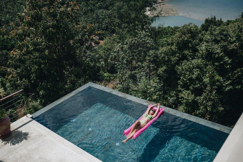 Προκλητική γυναίκα στο μπικίνι που απολαμβάνει το θερινό ήλιο στην πισίνα στοκ εικόνες