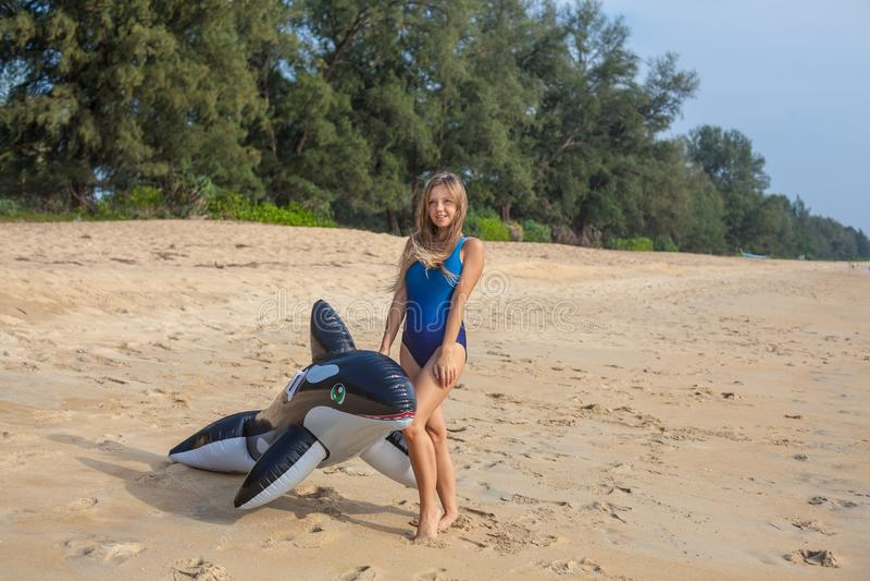 Προκλητική γυναίκα στο μπλε μαγιό στην παραλία με το διογκώσιμο παιχνίδι στοκ φωτογραφίες