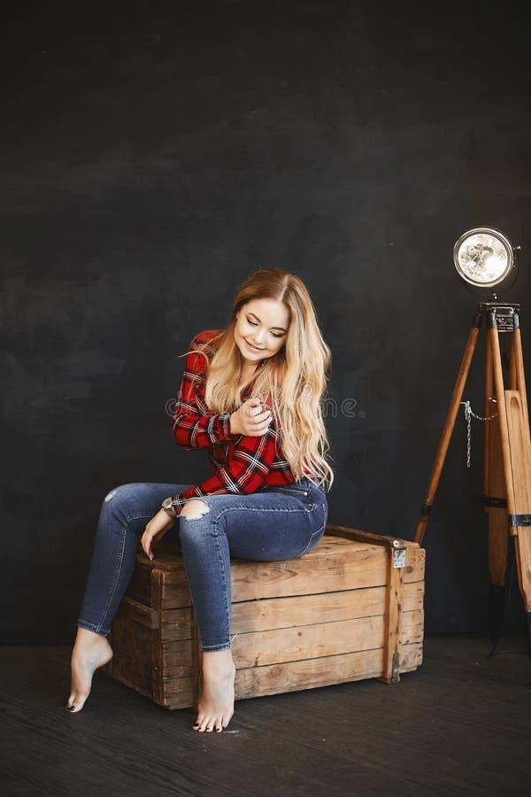 Προκλητική και όμορφη νέα γυναίκα, συν το πρότυπο κορίτσι μεγέθους με το φωτεινό makeup και με ξανθά μαλλιά στο κόκκινο πουκάμισο στοκ φωτογραφίες