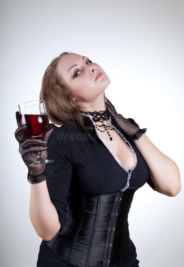 Προκλητική νέα γυναίκα με το ποτήρι του κόκκινου κρασιού στοκ εικόνα
