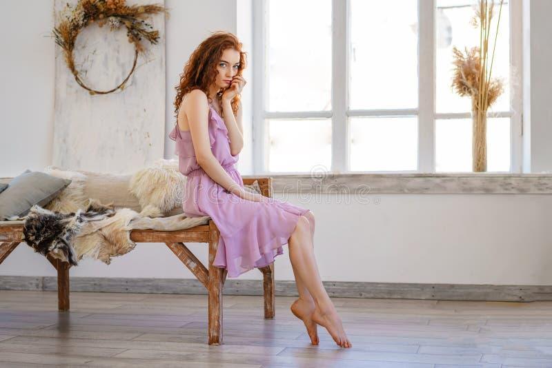 Προκλητική πολυτελής γυναίκα στη διεύθυνση Μόδα redhead στο όμορφο φόρεμα που θέτει τη συνεδρίαση στο στούντιο Όμορφη τρίχα και έ στοκ εικόνα