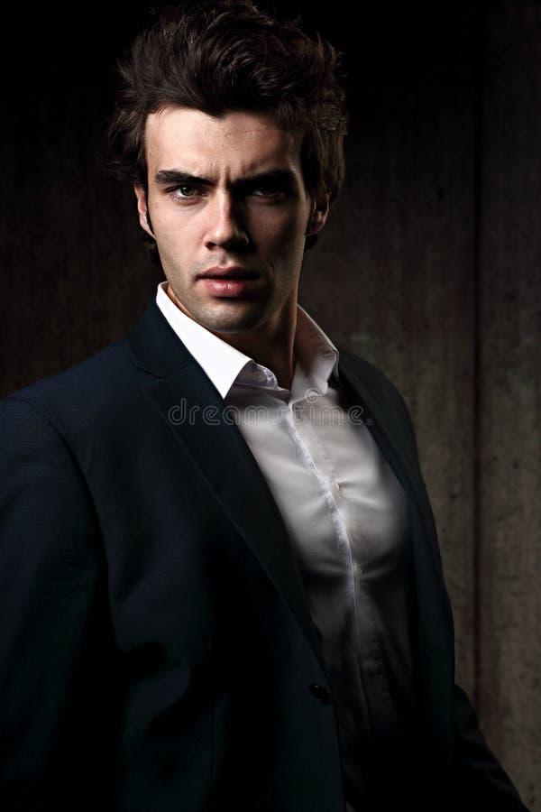 Προκλητική σοβαρή αρσενική τοποθέτηση επιχειρησιακών προτύπων στο μπλε κοστούμι και το άσπρο s στοκ εικόνες με δικαίωμα ελεύθερης χρήσης