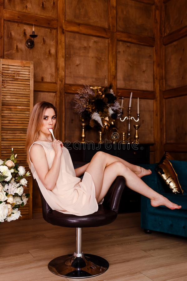 Προκλητική όμορφη νέα γυναίκα στην μπεζ συνεδρίαση φορεμάτων σε μια καρέκλα χωρίς παπούτσια και τα γλειψίματα ένα κουτάλι στοκ φωτογραφίες