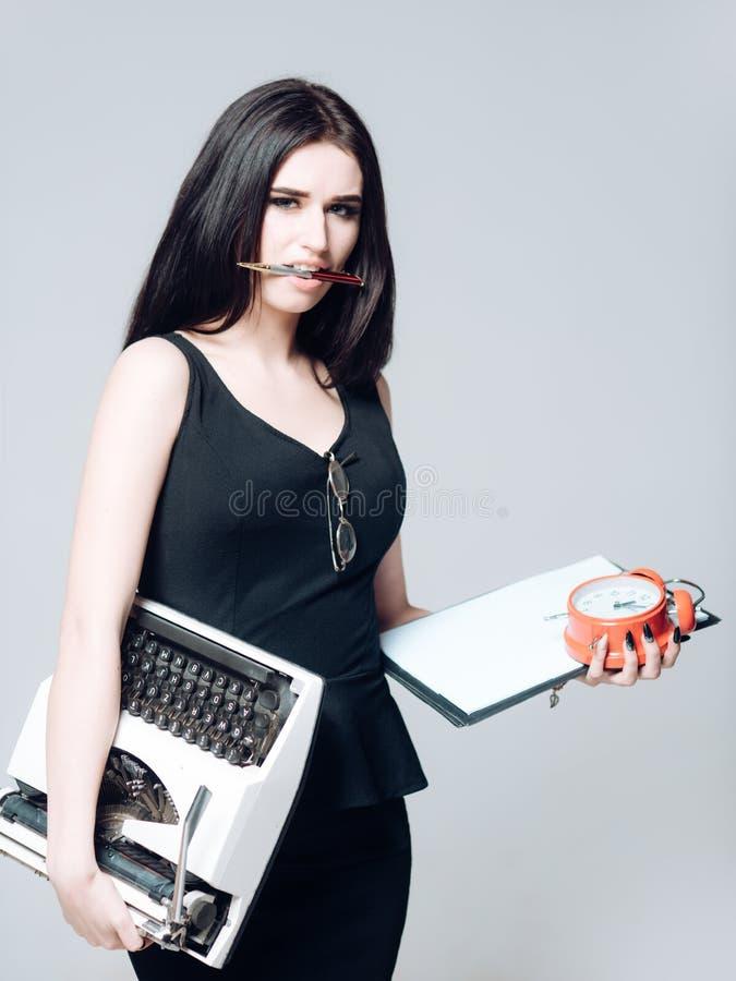 Προκλητικός γραμματέας με την περιοχή αποκομμάτων, το ρολόι και τη γραφομηχανή στα χέρια της Πολυάσχολη μάνδρα γυναικείας εκμετάλ στοκ εικόνες