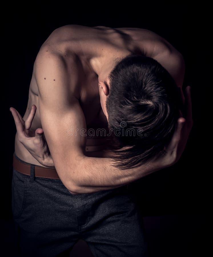 Προκλητικός μυϊκός νεαρός άνδρας στο σκοτεινό υπόβαθρο από την πλευρά με τα χέρια υπερυψωμένα στοκ εικόνες