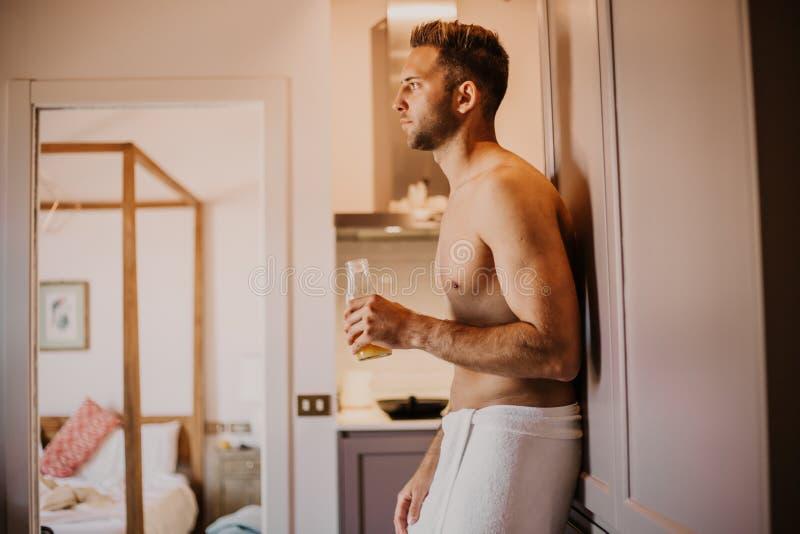 Προκλητικός νεαρός άνδρας με το γυμνό χυμό από πορτοκάλι χεριών εκμετάλλευσης κορμών, που φαίνεται έξω το παράθυρο και που χαμογε στοκ φωτογραφία με δικαίωμα ελεύθερης χρήσης