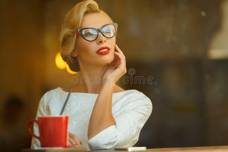 Προκλητικός ξανθός στο αναδρομικό βλέμμα που στηρίζεται στον καφέ στοκ φωτογραφία με δικαίωμα ελεύθερης χρήσης