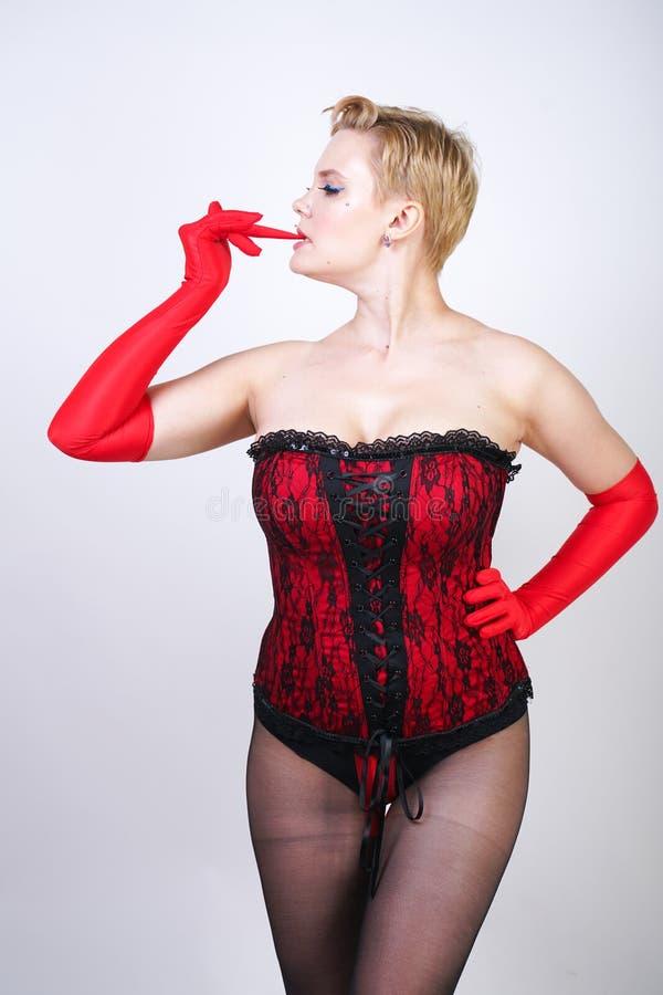 Προκλητικός συν τη γυναίκα μεγέθους με την κοντή τρίχα κόκκινο bodice δαντελλών και το καθαρό κλασικό μαύρο pantyhose με μια τοπο στοκ εικόνα με δικαίωμα ελεύθερης χρήσης