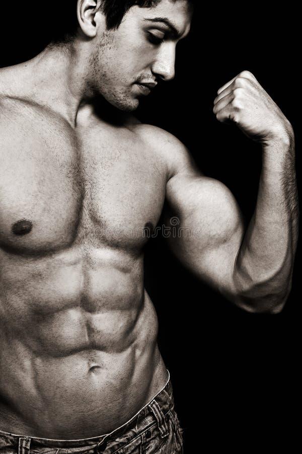 Προκλητικό άτομο με τους μυϊκούς δικέφαλους μυς και τα ABS στοκ εικόνες με δικαίωμα ελεύθερης χρήσης