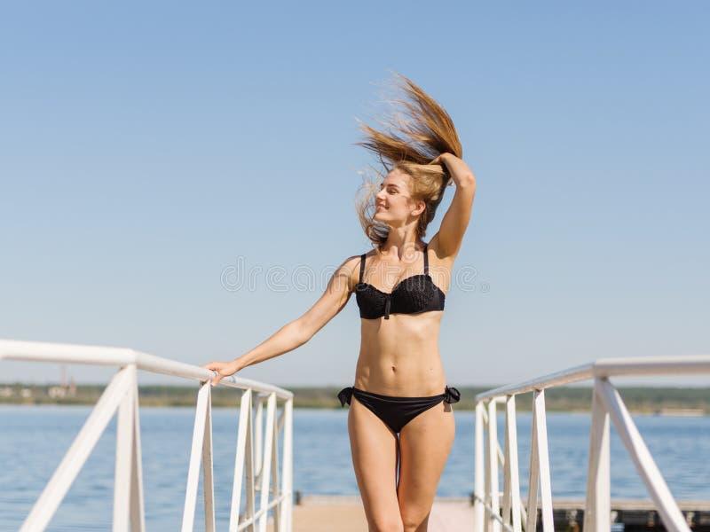 Προκλητικό θερινό κορίτσι με όμορφο μακρυμάλλη σε ένα υπόβαθρο μπλε ουρανού Έννοια Swimwear διάστημα αντιγράφων στοκ φωτογραφία