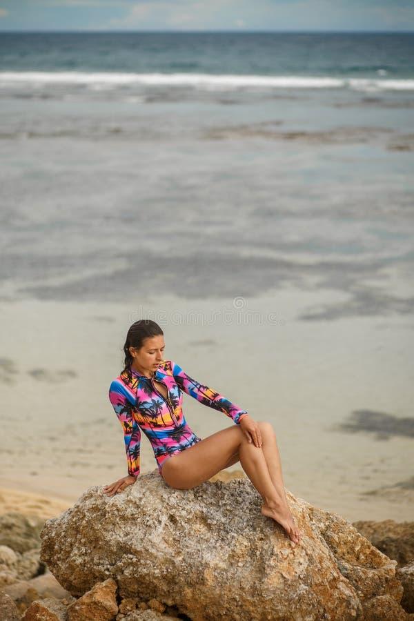 Προκλητικό κορίτσι που θέτει τη συνεδρίαση στους βράχους στην παραλία στοκ εικόνες