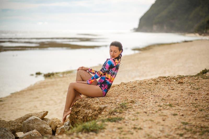 Προκλητικό κορίτσι που θέτει τη συνεδρίαση στους βράχους στην παραλία στοκ εικόνα με δικαίωμα ελεύθερης χρήσης