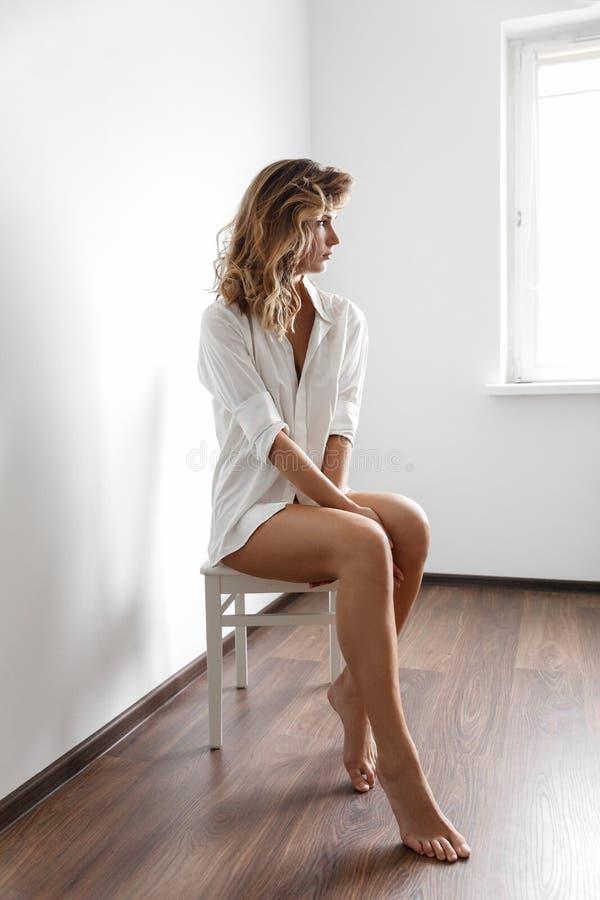 Προκλητικό κορίτσι στο άσπρο πουκάμισο σε μια άσπρη έδρα στοκ εικόνες