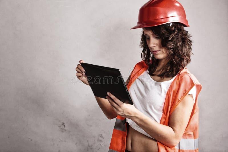 Προκλητικό κορίτσι στο κράνος ασφάλειας που χρησιμοποιεί την ταμπλέτα touchpad στοκ φωτογραφία με δικαίωμα ελεύθερης χρήσης