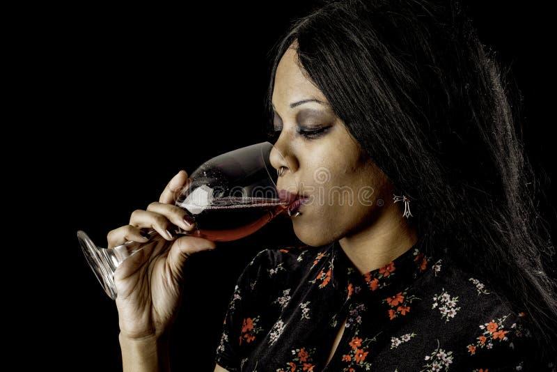 Προκλητικό κρασί κατανάλωσης μαύρων γυναικών στοκ φωτογραφία
