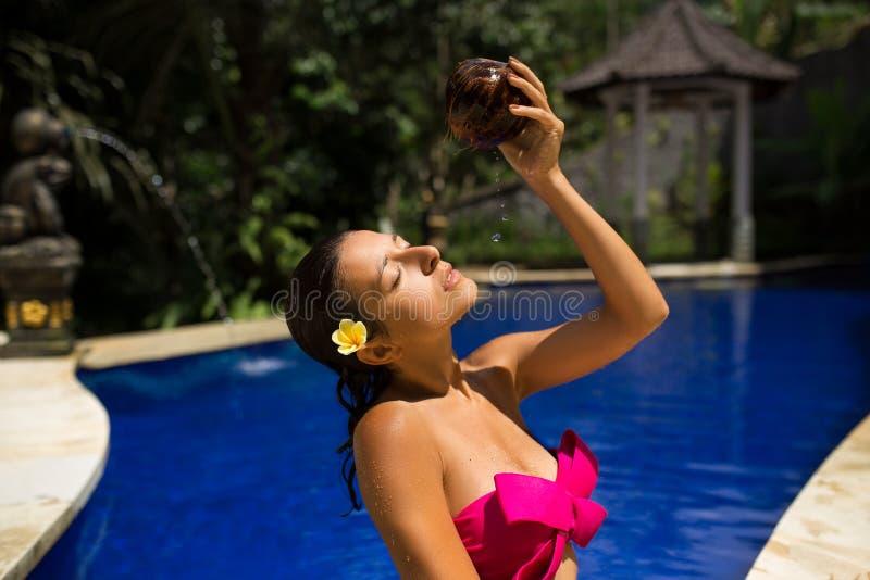 Προκλητικό λεπτό νέο θηλυκό brunette που ποτίζεται με το φρέσκο γάλα καρύδων στη λίμνη με το μπλε νερό κρυστάλλου Βασιλικό τροπικ στοκ φωτογραφία με δικαίωμα ελεύθερης χρήσης