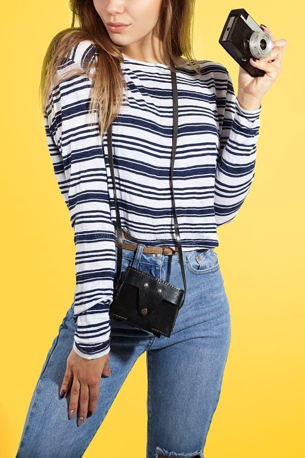 Προκλητικό νέο κορίτσι με την αναδρομική κάμερα στο κίτρινο υπόβαθρο στοκ εικόνες