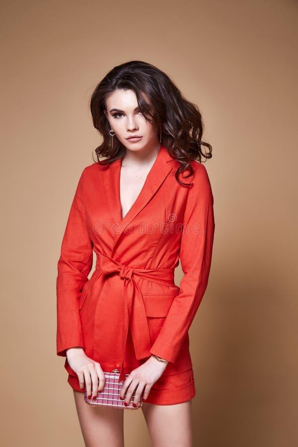 Προκλητικό ομορφιάς γυναικών όμορφο προσώπου μαυρίσματος δερμάτων σακάκι α κοστουμιών ένδυσης πορτοκαλί στοκ φωτογραφίες
