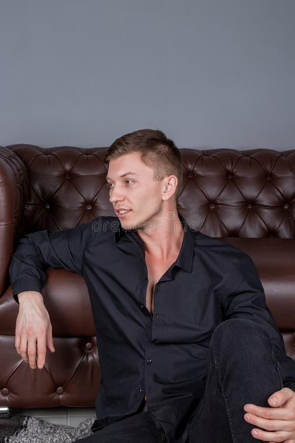 Προκλητικό όμορφο άτομο που φορά τη μαύρη συνεδρίαση πουκάμισων στο πάτωμα κοντά στον καναπέ δέρματος Άνεση και χαλάρωση στοκ εικόνες με δικαίωμα ελεύθερης χρήσης
