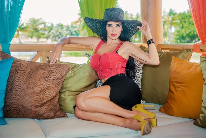 Προκλητικό brunette στο gazebo με τα μαξιλάρια στοκ φωτογραφία