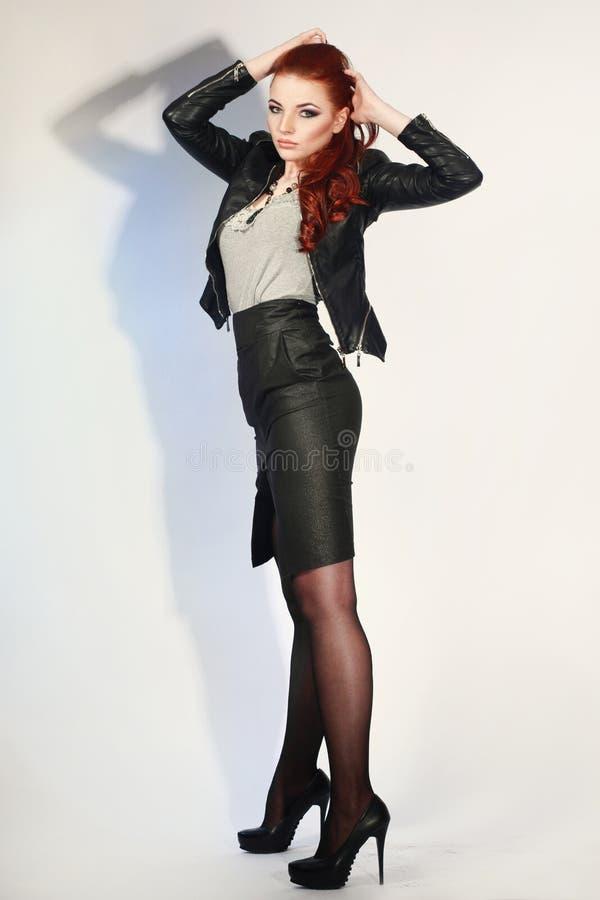 Προκλητικό redhead κορίτσι στο μαύρο φόρεμα στο άσπρο υπόβαθρο _ στοκ εικόνα