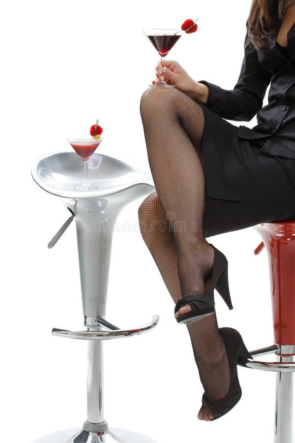 Προκλητικά θηλυκά πόδια στα υψηλά τακούνια στο φραγμό κοκτέιλ στοκ εικόνες