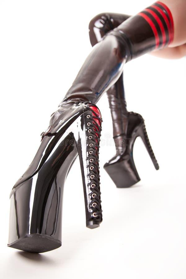 Προκλητικά μακριά πόδια στις γυναικείες κάλτσες λατέξ και τα υψηλά τακούνια στοκ εικόνες