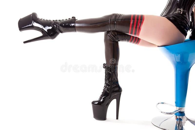 Προκλητικά μακριά πόδια στις γυναικείες κάλτσες λατέξ και τις υψηλές μπότες τακουνιών στοκ φωτογραφία με δικαίωμα ελεύθερης χρήσης
