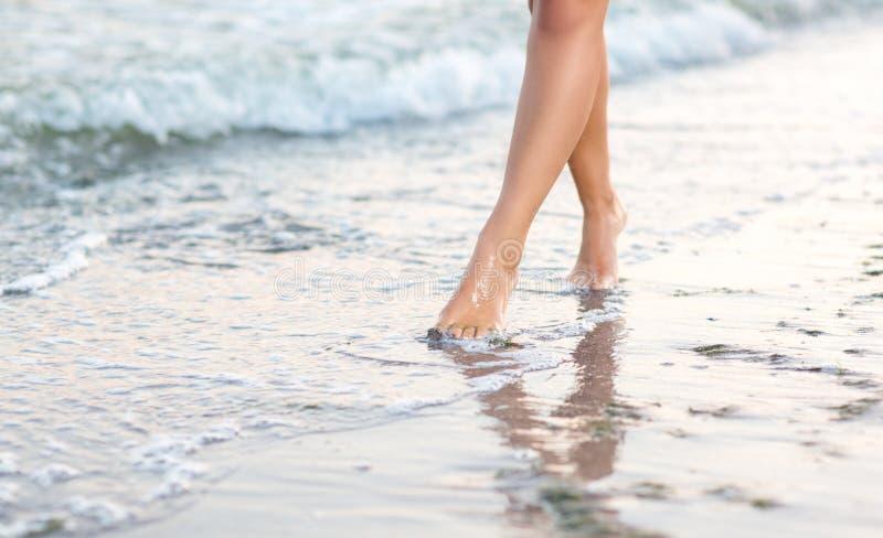 Προκλητικά πόδια γυναικών ` s κοντά στη θάλασσα στην άμμο Όμορφα πόδια ενός λεπτού κοριτσιού Το πόδια αθλητριών ` s στοκ φωτογραφία με δικαίωμα ελεύθερης χρήσης