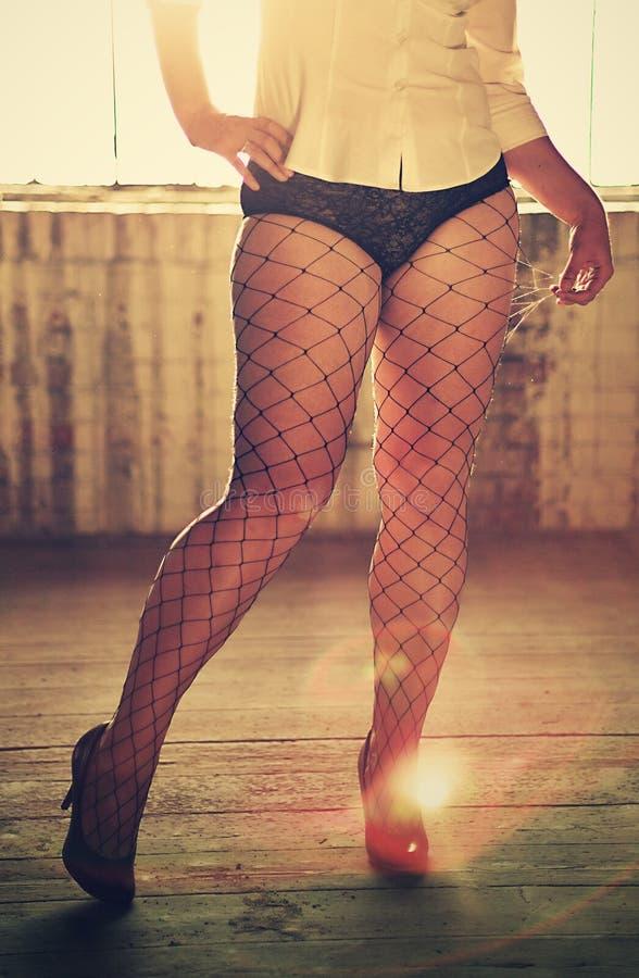 Προκλητικά πόδια στις γυναικείες κάλτσες διχτυών ψαρέματος στοκ εικόνες
